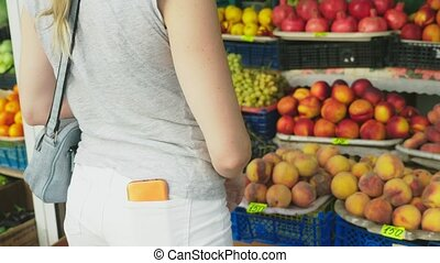 A woman is choosing vegetables in the market. 4k. Slow...