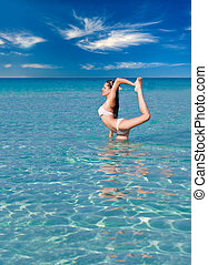 A woman is doing flexibility exercise in the sea