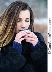 A woman is drinking a hot drink