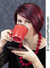A woman is drinking from a red cup.