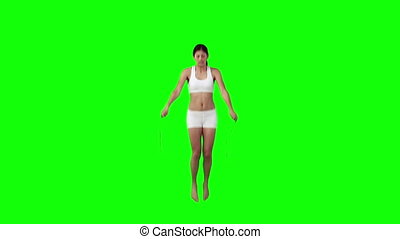 A woman is exercising with a skipping rope against a green...