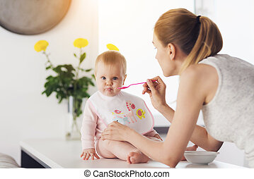 A woman is feeding a baby with a spoon. A child sits on a...