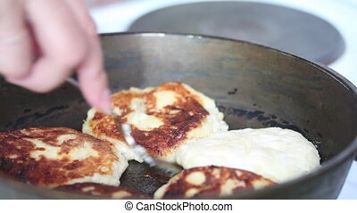 A woman is frying cheese cakes in a frying pan. Turn them...