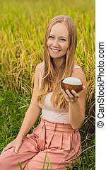A woman is holding a cup of boiled rice in a wooden cup on the background of a ripe rice field VERTICAL FORMAT for Instagram mobile story or stories size. Mobile wallpaper
