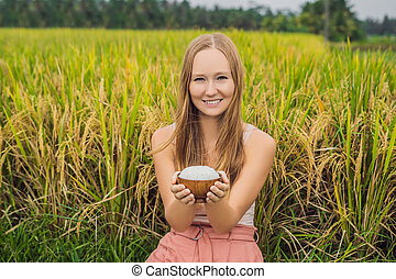 A woman is holding a cup of boiled rice in a wooden cup on the background of a ripe rice field