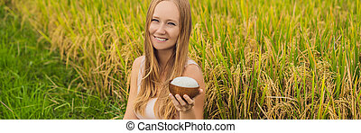 A woman is holding a cup of boiled rice in a wooden cup on the background of a ripe rice field BANNER, LONG FORMAT
