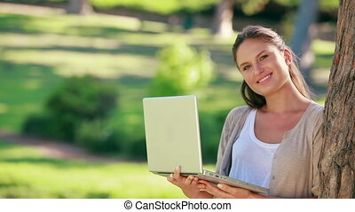 A woman is holding a laptop