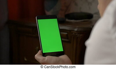 A woman is holding a smartphone with a green screen while lying on the bed.