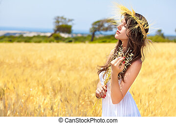 A woman is in the field with a wreath