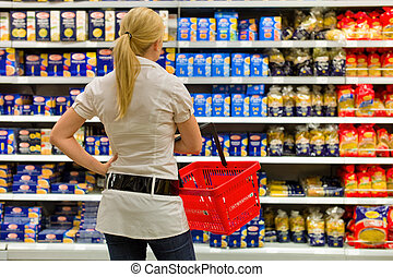 selection in a supermarket - a woman is overwhelmed with the...