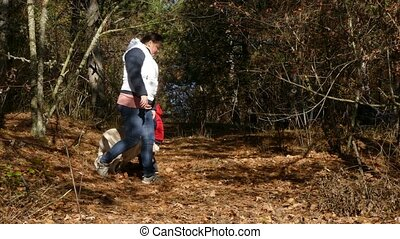 A woman is playing with a dog in the forest.