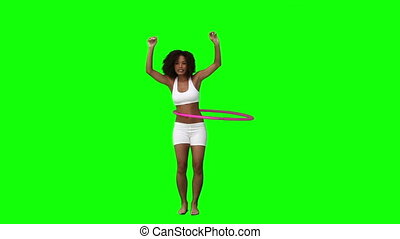 A woman is playing with a hula hoop
