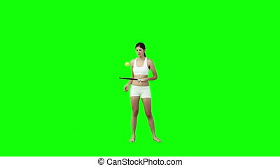 A woman is playing with a tennis racket and ball