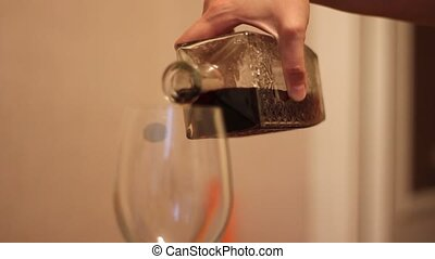 A woman is pouring red wine.
