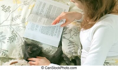 A woman is reading a book in bed, a gray cat is lying next to her