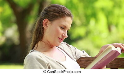 A woman is reading a book on a bench