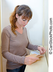 a woman is reading letter