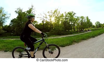 A woman is riding a bicycle in the park. Slow motion.