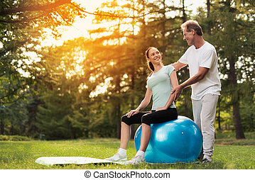 A woman is sitting on a ball for yoga. A man is standing behind and looking at her.