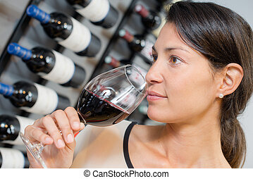 a woman is smelling wine