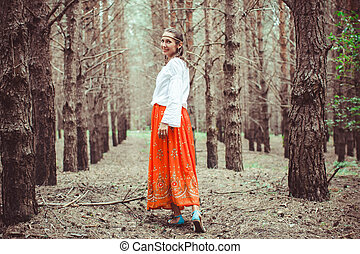 A woman is standing between trees