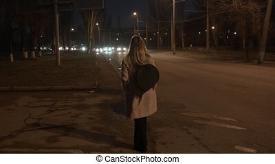A woman is standing in a coat near the road at night. Car rushing past. A young woman is waiting for her to pick up a taxi.