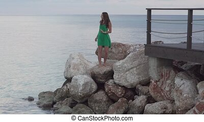 A woman is standing on rocks near the sea