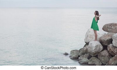 A woman is standing on rocks near the sea.