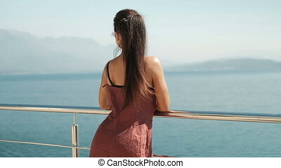 A woman is standing on the balcony with a glass and looking at the sea