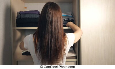 A woman is tidying up the closet. Young girl put clothing...