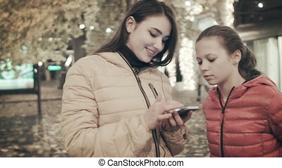 A woman is using a smartphone along with her daughter on a city street at night.