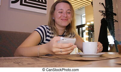 A woman is using the phone in a cafe with a cup of coffee