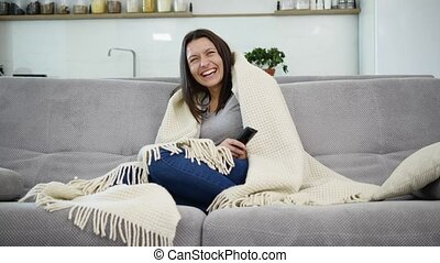 A woman is watching TV with a blanket