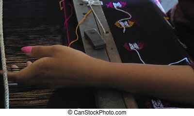 A woman is weaving a tapestry