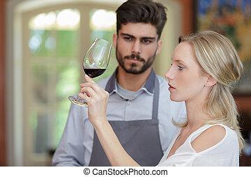 a woman is wine tasting