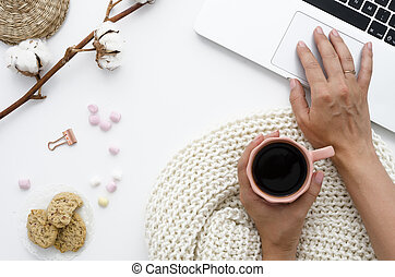 A woman is working behind a laptop and is holding coffee. On the table lie oatmeal cookies, marshmallow and cotton flowers. Autumn or Winter concept. Flat lay, top view