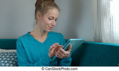 A woman is working happily on a tablet while sitting on the couch.