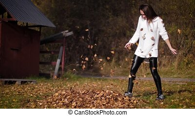 A woman kicks leaves in autumn, launching them everywhere. Girl kicks on a pile of dry autumn leaves. 4k 60fps slow motion
