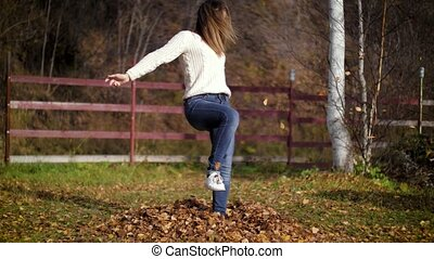 A woman kicks leaves in autumn, launching them everywhere. Girl kicks on a pile of dry autumn leaves. 4k 60fps slow motion. Autumn fun.