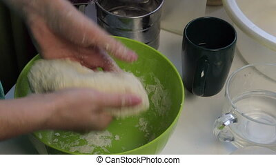 A woman kneads dough in her hands. Cooking bread at home.