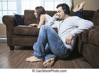 A woman lay on the sofa with laptop and a man ear music
