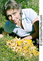 A woman lies on a lawn near the cha