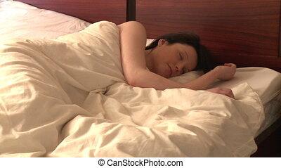 A woman looking at alarm clock - Snoozing woman looking at...