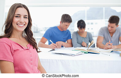A woman looking at the camera as her friends sit behind her and study together