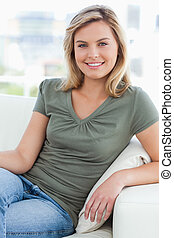 A woman looking forward with her arm on the couch arm and smiling.