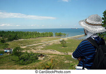 a woman looking out to sea from the top of the hill