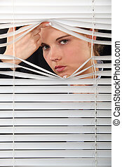 A woman looking through the blinds