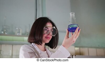 A woman looks at the blue water in medical laboratory