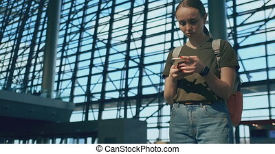 A woman looks at the screen of a mobile phone to find your...