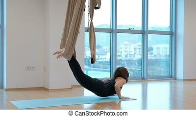 A woman lying doing an exercise with a hammock for air yoga....